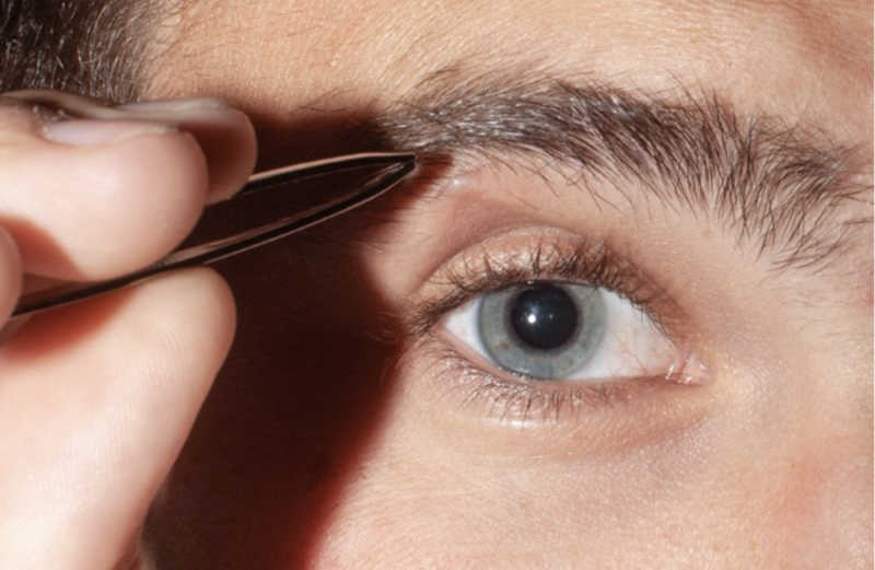 Closeup of person plucking eyebrows