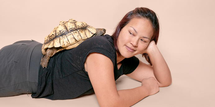 A woman laying on her stomach poses with a turtle on her back.