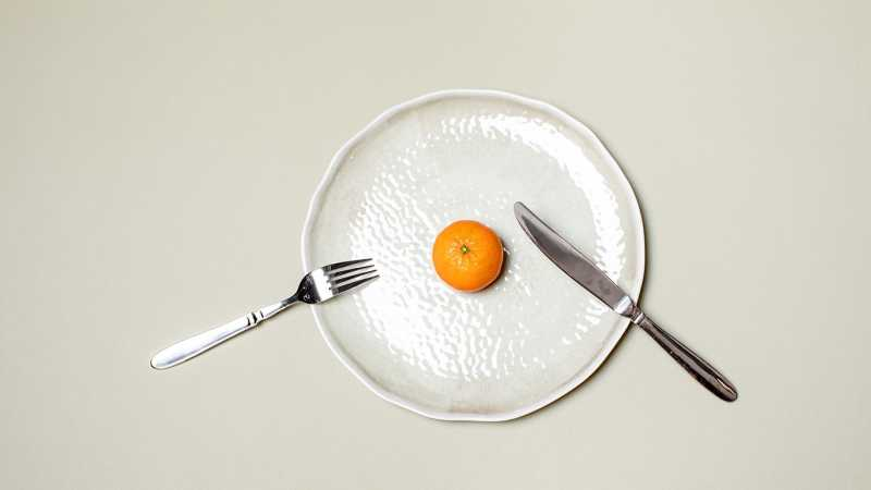 Orange on white plate with silverware