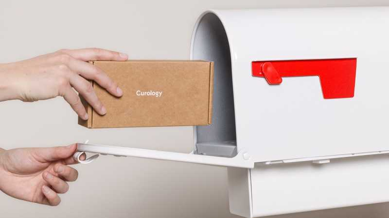 Curology box being placed in white mailbox