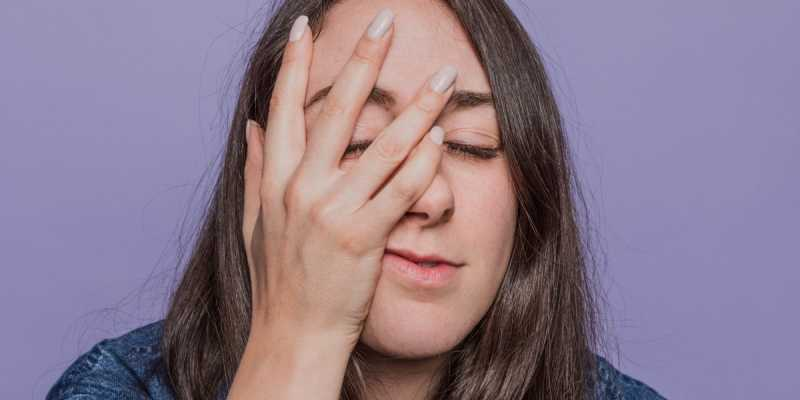 Woman with hand on her face and purple background