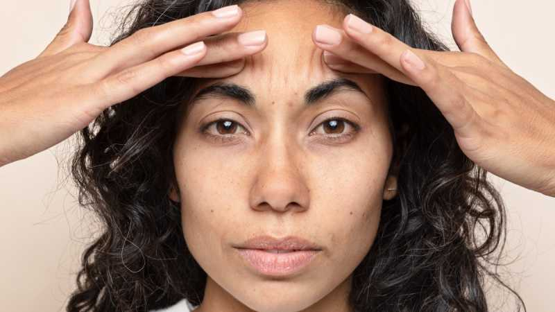 Woman pushing fingers into forehead to create wrinkles