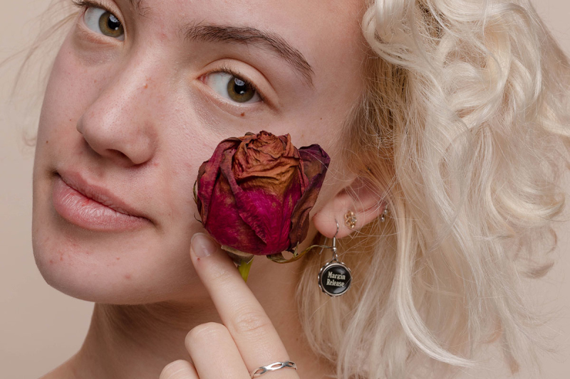 Woman holding dried rose next to cheek against a pale neutral background