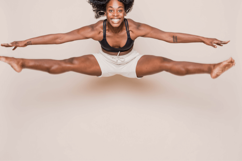 Woman in a sports bra and shorts jumping into a split against a light neutral background