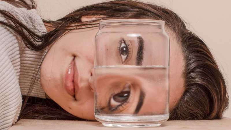 Woman with head on surface looking at glass of water