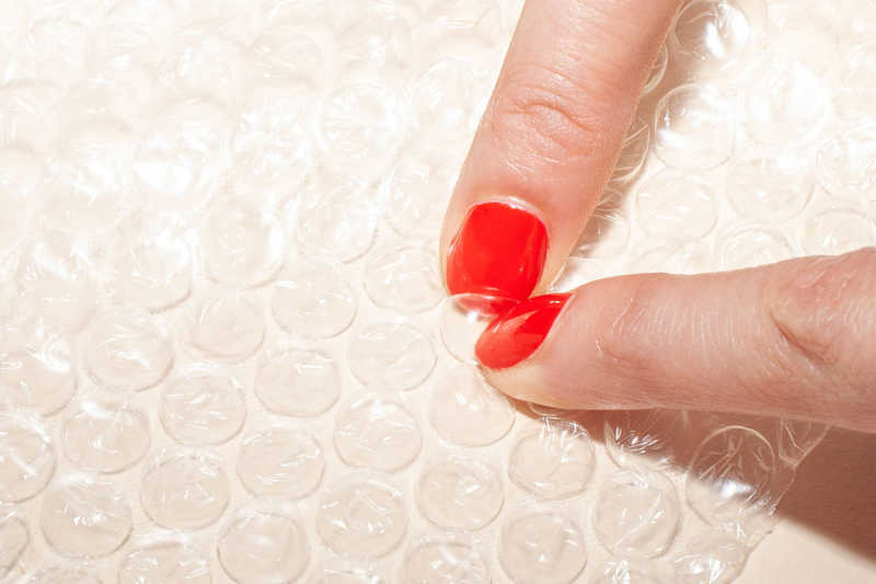 Fingers with red nail polish popping bubble wrap against a neutral background