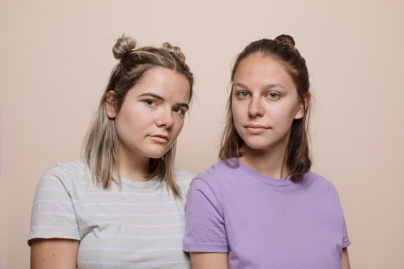 Women looking at camera with neutral background. Purple shirt and striped shirt