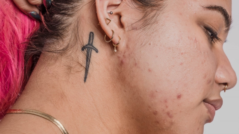 Woman with knife tattoo on her neck