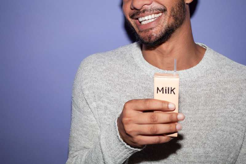 Man holding milk carton with purple background smiling