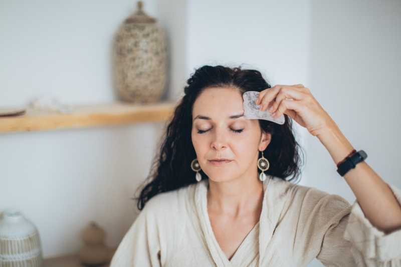Woman using heart shaped stone on forehead