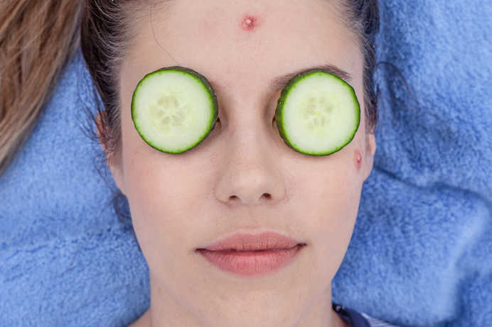 Close-up of a woman's face. She is laying on a blue towel with cucumbers resting on her eyes.