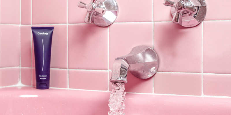 Curology cleanser on pink bathtub with running water and pink tile background