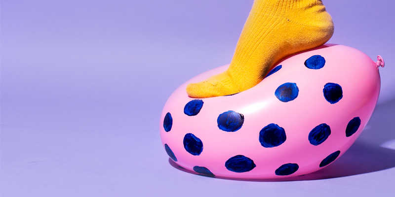 Closeup of foot in a yellow sock stepping and pressing a pink balloon with blue dots, all against a purple background