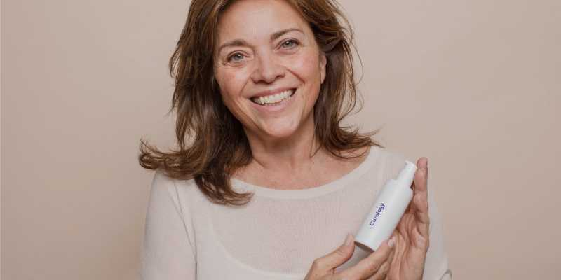 A woman smiling and looking into the camera while holding a bottle of Curology cream