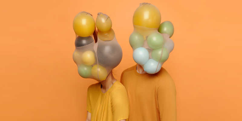 Two people in yellow and orange shirts with yellow, green, and blue balloons in place of heads, all against an orange background
