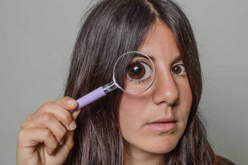Portrait of a woman holding a magnifying glass in front of her eye so that it looks comically large