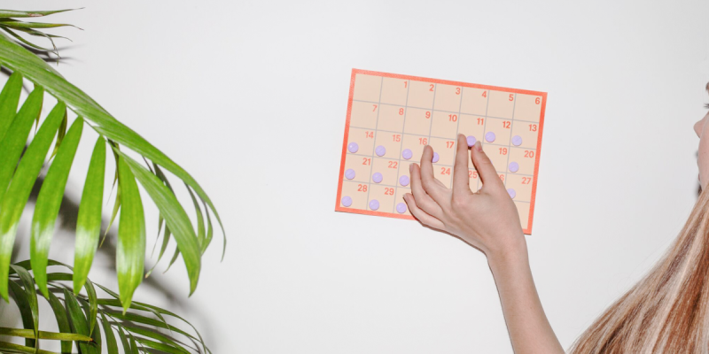 Person placing pill on calendar
