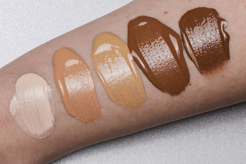 Swatches of different tones of concealer on someone's inner arm. The swatches are organized from lightest to darkest.