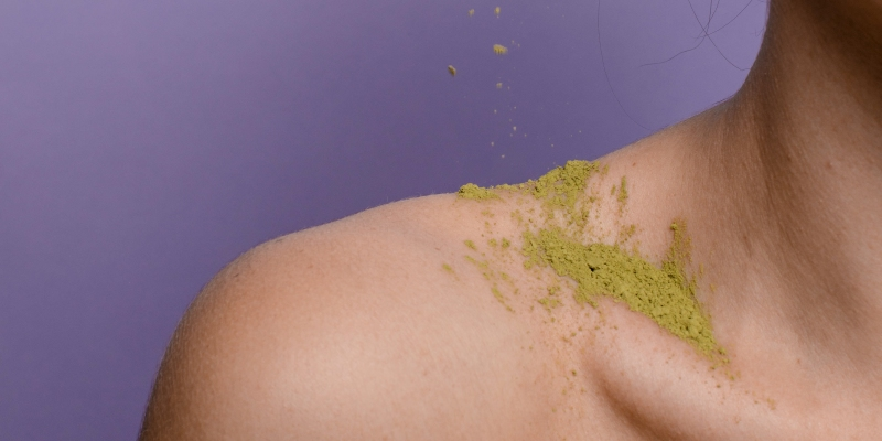 Closeup of collarbone and shoulder with green powder against a purple background