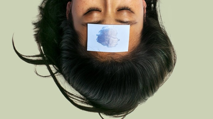 Woman with blue paper on forehead upside down
