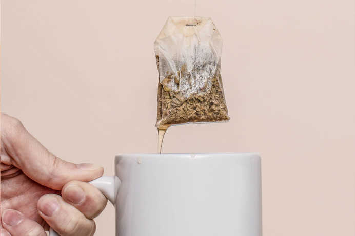 Closeup of hand holding white mug below tea bag against a neutral background