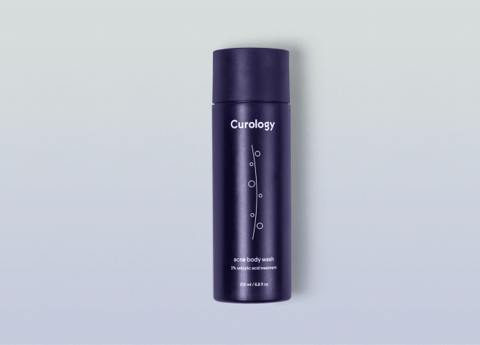 Curology Acne Body Wash bottle against a neutral gray background
