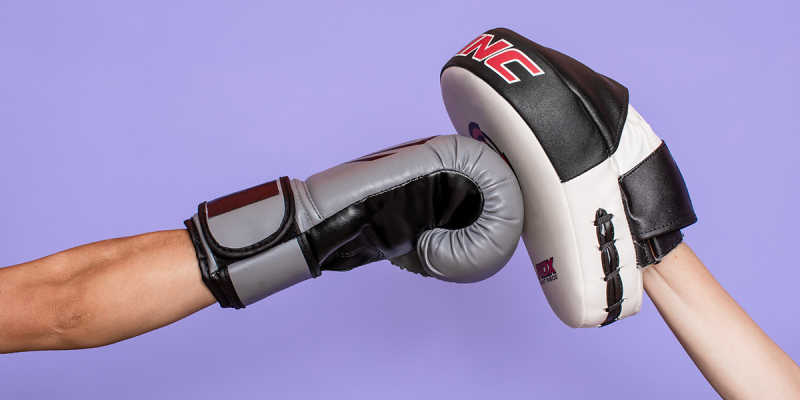Two arms in boxing gloves, arm on the left punching the hand on the right, all against a purple background