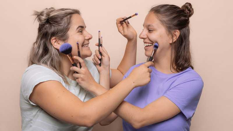 Two women with pressing brushes into their faces