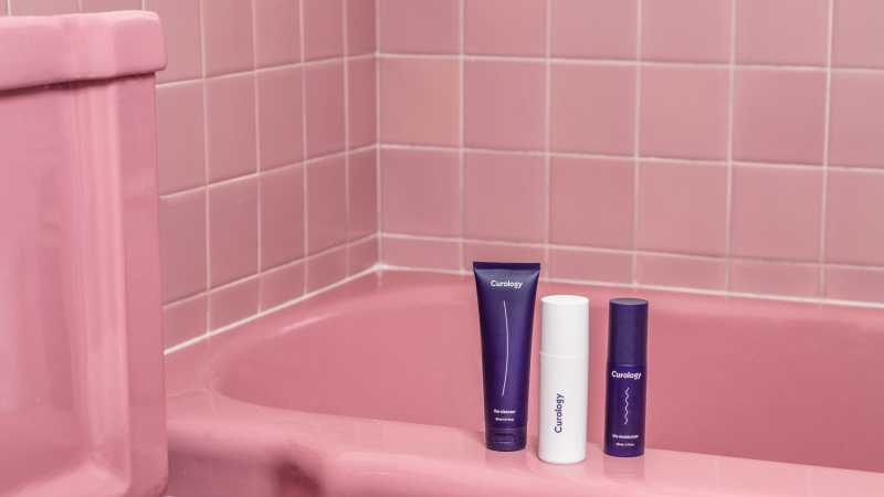 Curology bottles next to pink tiled bathtub in bathroom