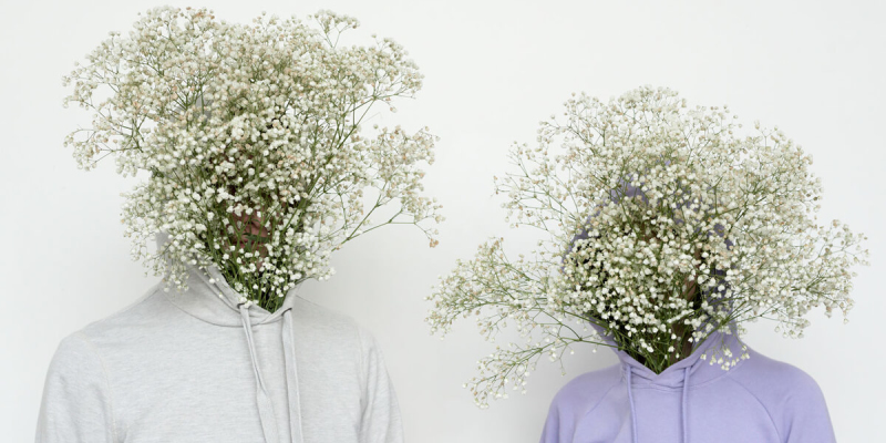 Two bodies in a white and purple hoodie with white flowers instead of faces, against a white background