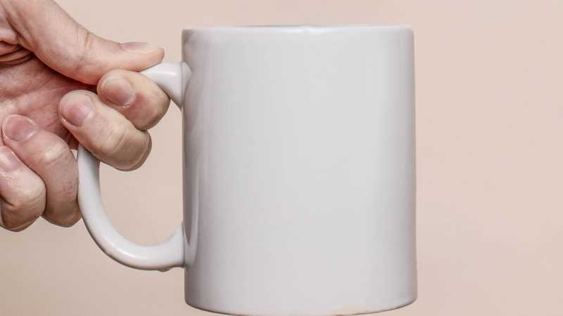 Hand holding white mug with neutral background