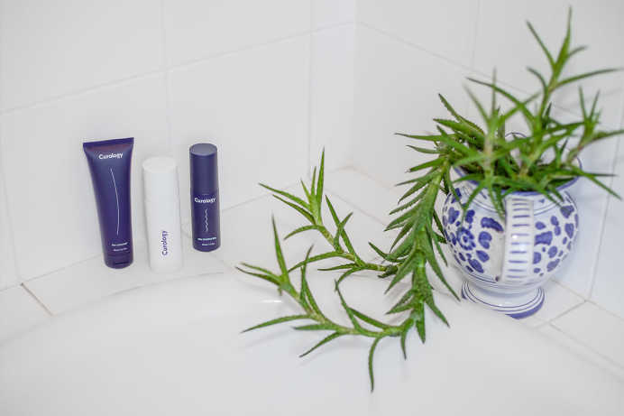 Photograph of a bathtub corner. The Curology set is on the left. An overgrown houseplant is on the right.