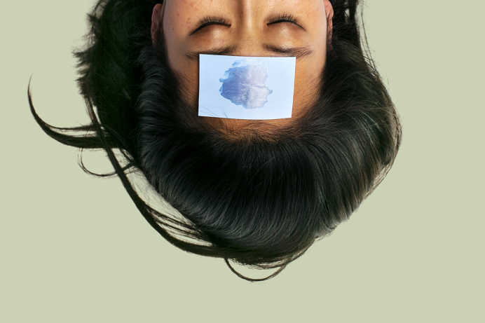 Woman with black hair upside-down with blue blotting paper on forehead against a