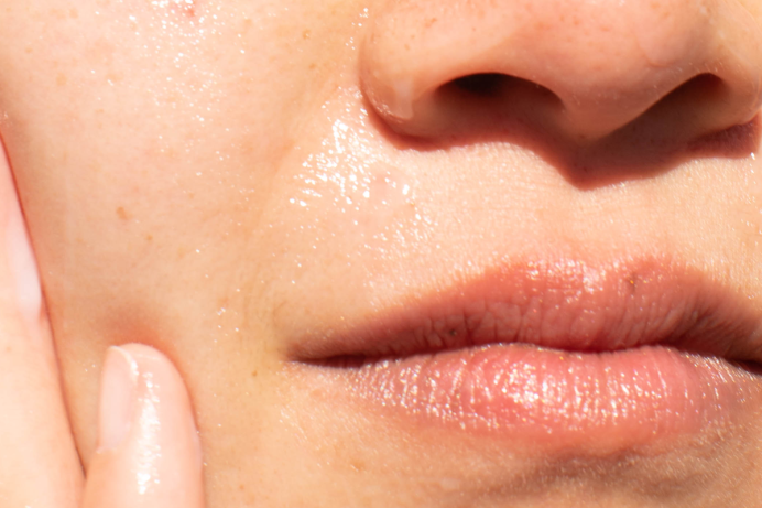 Closeup of dewy nose and mouth with finger on cheek
