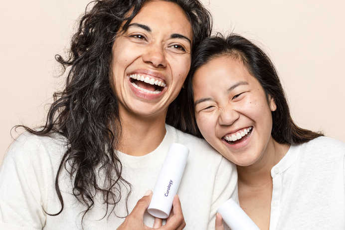 Two women laughing and leaning on each other while holding bottles of Curology custom cream