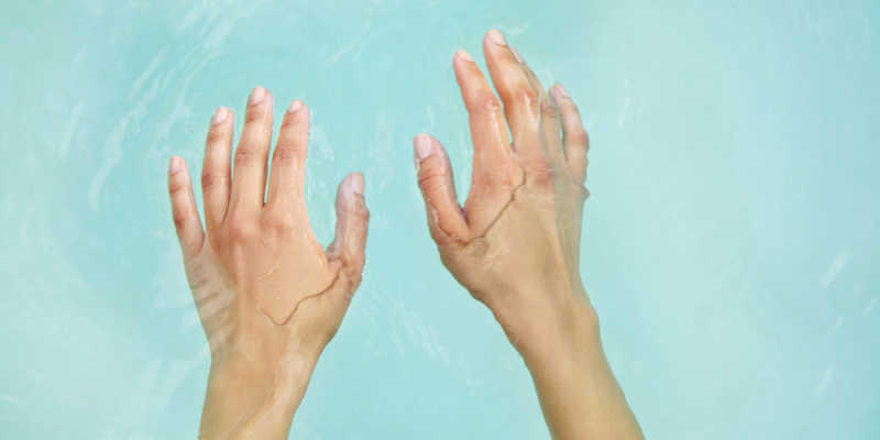 A pair of hands, half-submerged in light blue water.