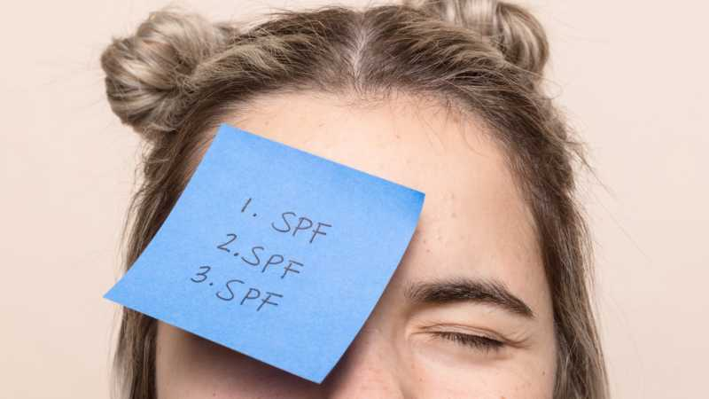 Woman with spf sticky note on her face