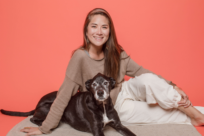 Woman and dog sitting with orange background
