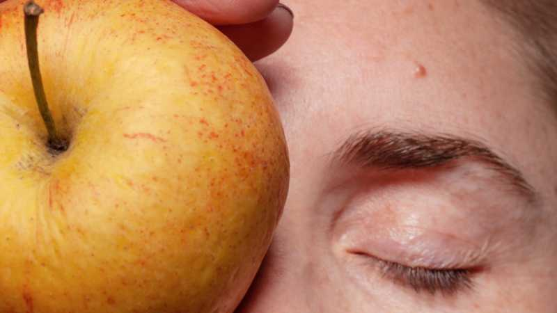 Closeup of person with apple on their face