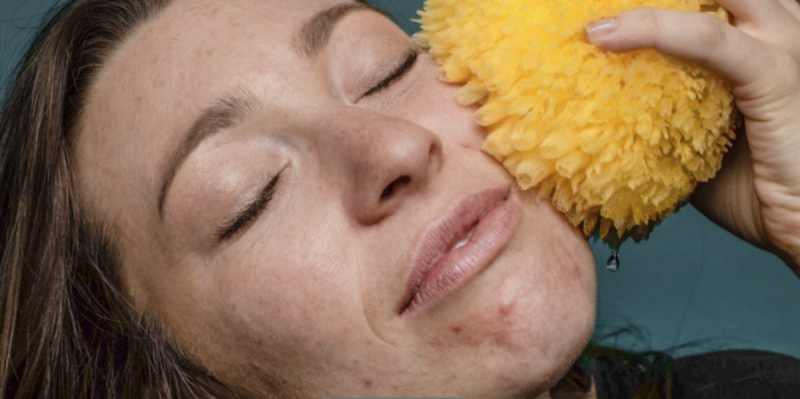 Woman with sponge on her face