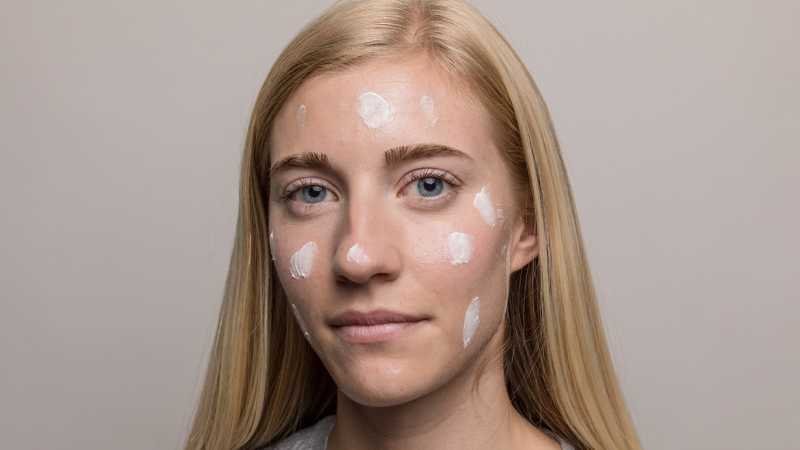 Closeup of woman with skincare cream in spots around face