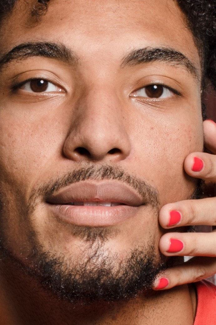 Closeup of man with a hand touching his face (with red fingernails)
