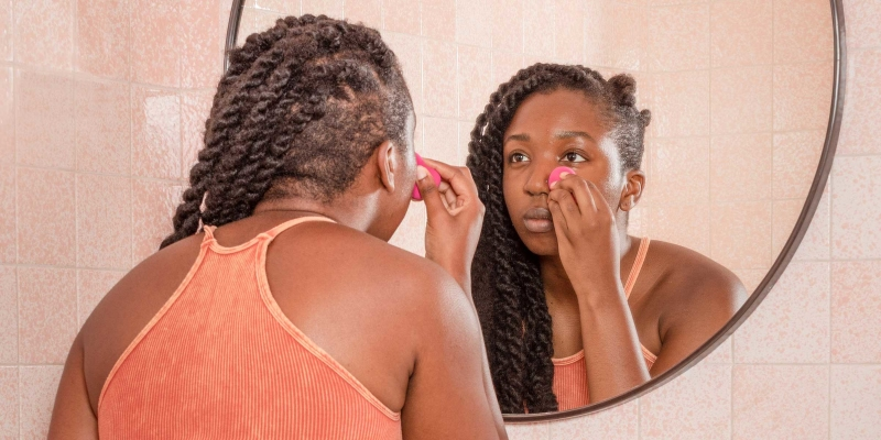 Woman in peach colored top looking in round mirror and applying makeup to face with a pink sponge