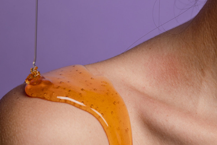 Closeup of a shoulder with golden liquid against a purple background