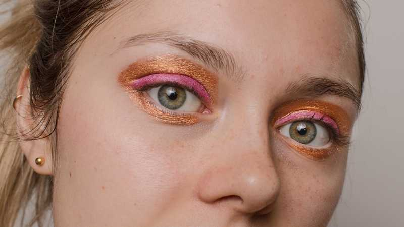 Closeup of woman with orange and pink eyeshadow