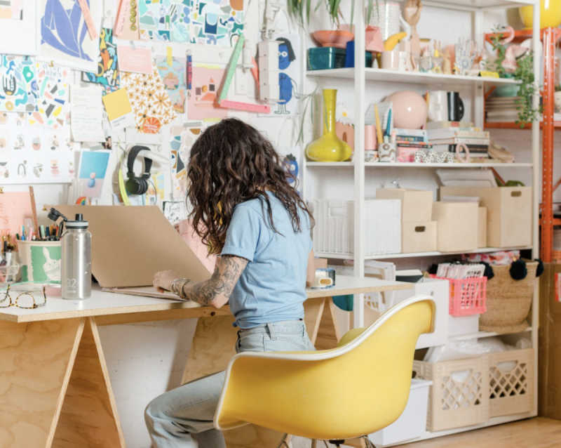 Woman sitting at desk working on art