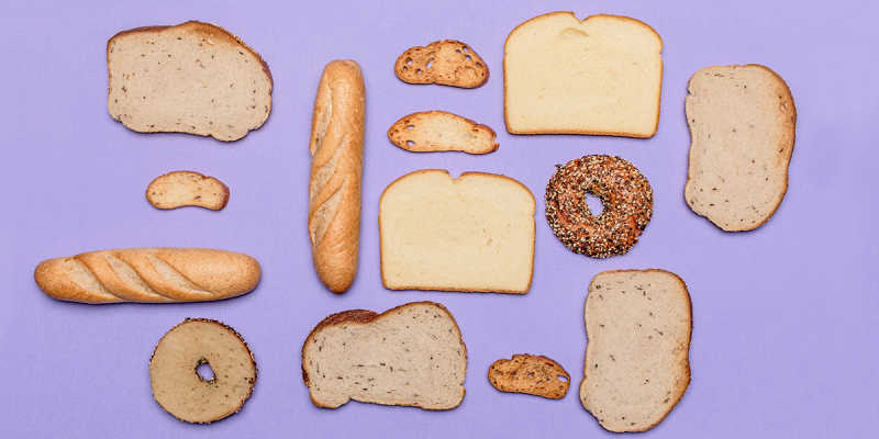 Slices and loaves of breads of various sizes and types against a purple background