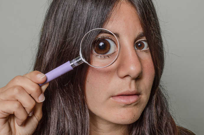 A woman holding a magnifying glass over one of her eyes