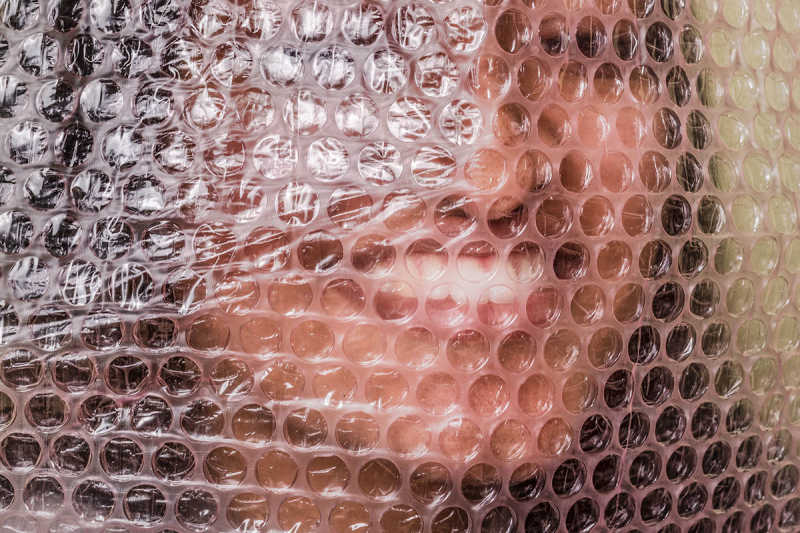 Closeup of woman's face behind bubble wrap