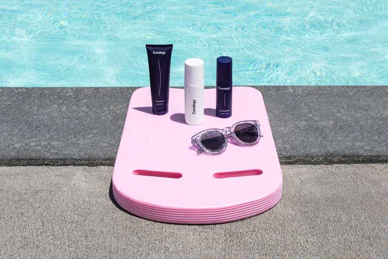 The Curology set sitting on top of a boogie board with sunglasses. A swimming pool is in the background.